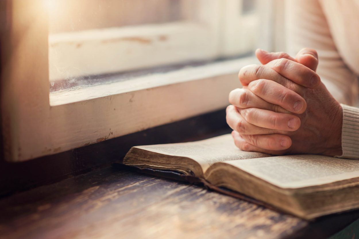 Hands of an unrecognizable woman with Bible praying